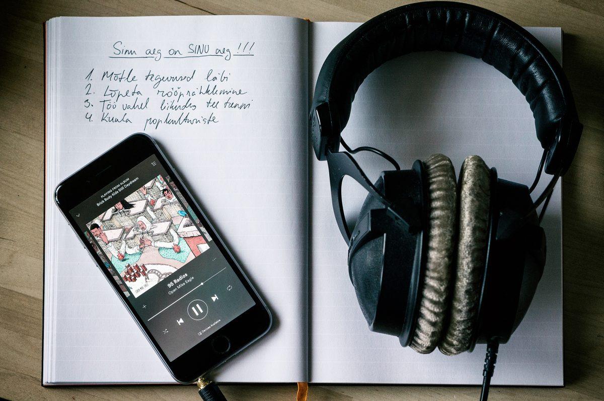 Märkmit, telefon ja kõrvaklapid laual